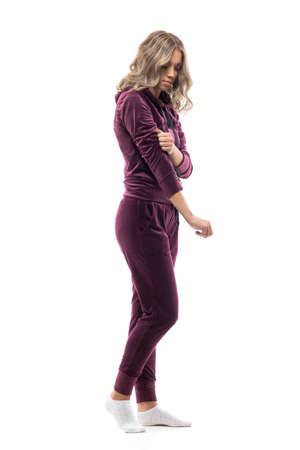 Young woman at home in socks getting dressed in burgundy tracksuit leisurewear. Full body isolated on white background.