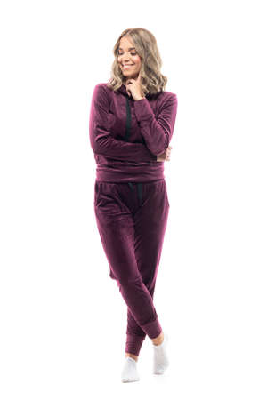 Happy young pretty woman in burgundy sweatsuit having idea looking down with finger on cheek. Full body isolated on white background. 免版税图像
