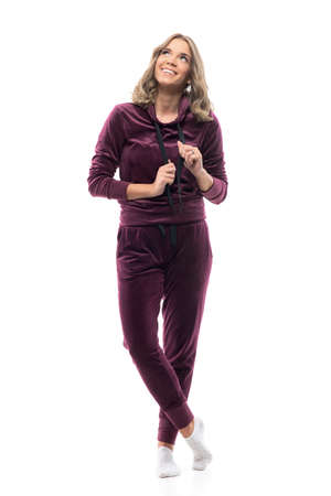 Happy young beautiful woman in burgundy hooded tracksuit looking up and smiling at home. Full body isolated on white background.