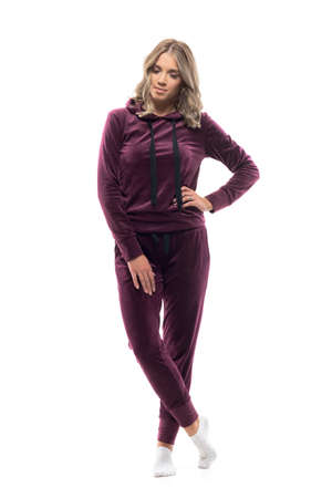 Longing thoughtful woman in maroon tracksuit home wear looking down with hand on hip. Full body isolated on white background.