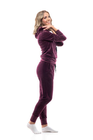 Side view of happy beauty at home getting dressed in burgundy leisurewear in ankle socks. Full body isolated on white background.
