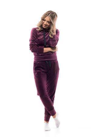 Cute shy happy woman in casual leisurewear tracksuit smiling having happy thoughts. Full body isolated on white background.