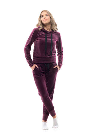 Relaxed young beauty woman with hands in pockets wearing socks and tracksuit looking up. Full body isolated on white background.