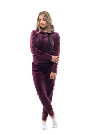Young woman at home in leisure wear sweatsuit looking down contemplating. Full body isolated on white background.