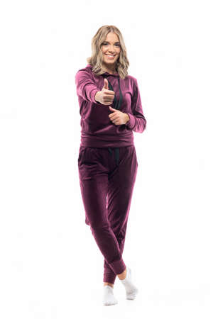 Positive friendly young woman in maroon leisurewear tracksuit showing thumb up hand sign. Full length isolated on white background.