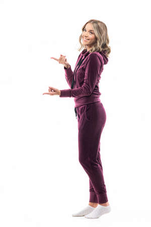Side view of happy young woman in casual tracksuit home wear pointing fingers at copyspace. Full length isolated on white background.