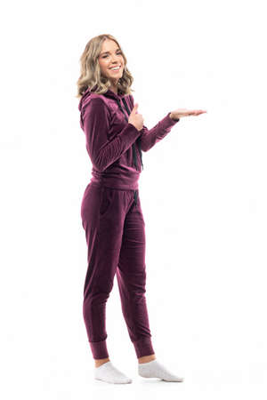 Happy young woman in maroon casual hooded tracksuit showing at copy space with thumb up. Full length isolated on white background.