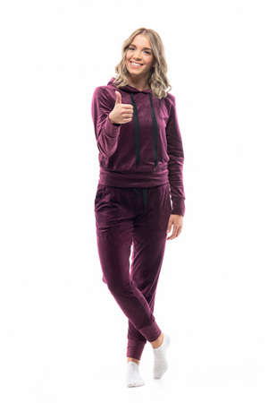 Cheerful young woman in cozy sweatpants and hooded shirt showing thumb up at camera. Full length isolated on white background.