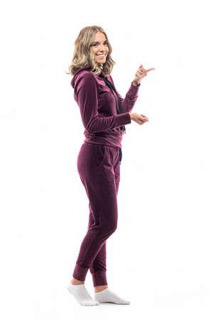 Happy girl in maroon hooded sweatsuit pointing finger at copy space smiling at camera. Full length isolated on white background. 免版税图像