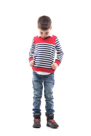 Sad disappointed little kid with bowed head looking down and complaining. Full body portrait isolated on white background. Standard-Bild