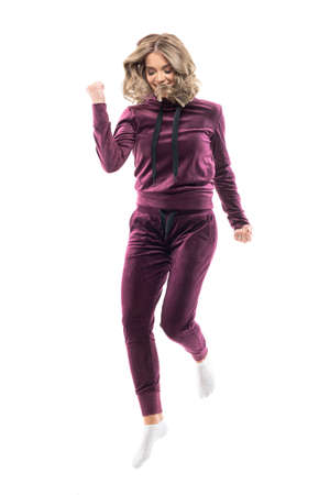 Beautiful young successful woman in home wear leisure clothes jumping with clenched fists looking down. Full body length isolated on white background.