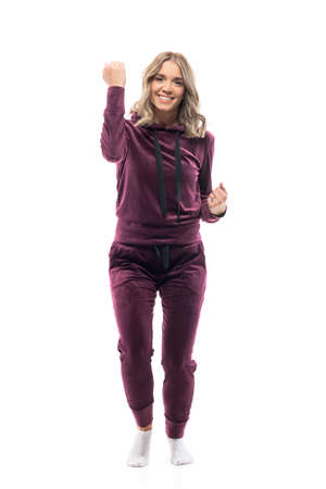 Cheerful young beautiful woman in burgundy sweatsuit and socks raise hand successfully smile at camera. Full body length isolated on white background.