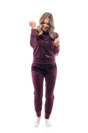 Happy excited young woman in leisurewear sweatsuit celebrating success with clenched fists. Full body length isolated on white background.
