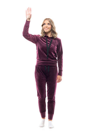 Happy young woman in home comfy clothes reaching up and taking or grabbing with raised hand. Full body length isolated on white background.