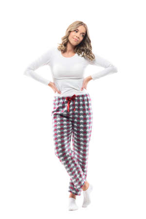 Beautiful young woman in pajama posing with hands on hips looking away and smile. Full body length isolated on white background. Stock fotó