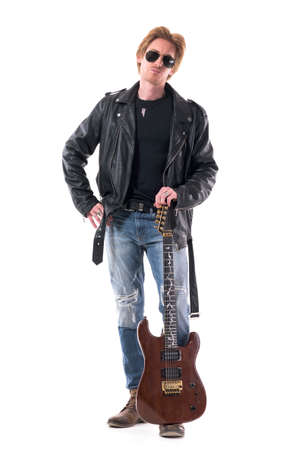 Confident young handsome redhead rock musician posing and holding electric guitar on leg. Full body isolated on white background.