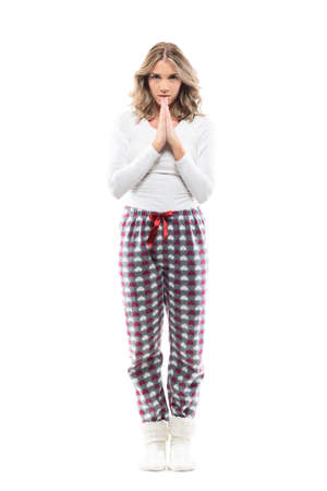 Young serious woman pleading staring at camera with praying hands in pajama. Full length portrait on white background. Reklamní fotografie