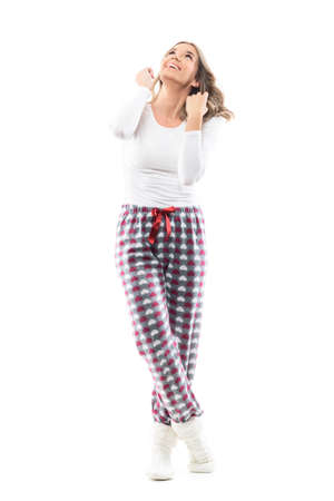 Young happy woman in cozy pajama and winter socks watching above attracted. Full length portrait on white background.