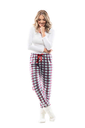 Happy shy young beautiful woman smiling after compliments looking down in pajama and socks. Full length portrait on white background. Stock Photo