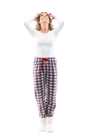 Carefree young beautiful woman in pajama and socks at home looking up with hands in hair. Full length portrait on white background.