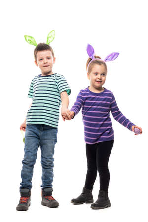Cheerful excited two children boy and girl with Easter eggs and bunny hat holding hands and smiling. Full body isolated on white background Stockfoto