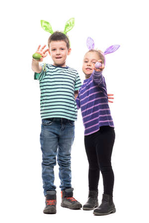Happy two kids boy and girl with bunny ears holding Easter eggs waving hello at camera. Full body isolated on white background Stockfoto