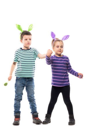 Cute excited girl and young boy with Easter bunny ears holding painted eggs holding hands. Full body isolated on white background