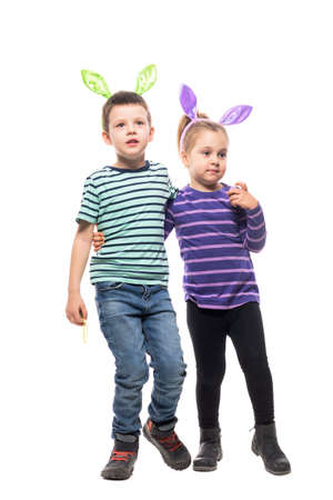 Boy and girl siblings with Easter bunny hat hugging and looking away watching. Full body isolated on white background Stockfoto