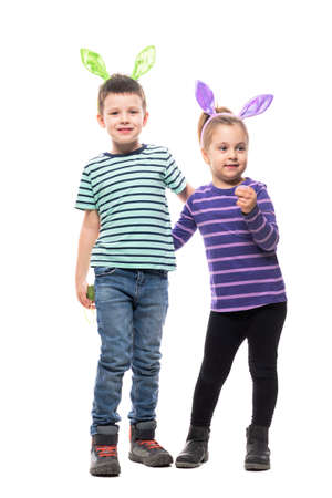 Cute two children boy and girl hugged wearing Easter bunny ears posing at camera. Full body isolated on white background Stockfoto
