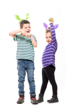 Cute young boy and girl with bunny ears playing candid and posing with Easter eggs. Full body isolated on white background