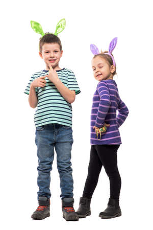 Cute boy and girl with bunny ears for Easter posing and smiling at camera. Full body isolated on white background