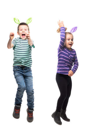 Excited cheerful jumping kids boy and girl in Easter bunny ears hat action. Full body isolated on white background