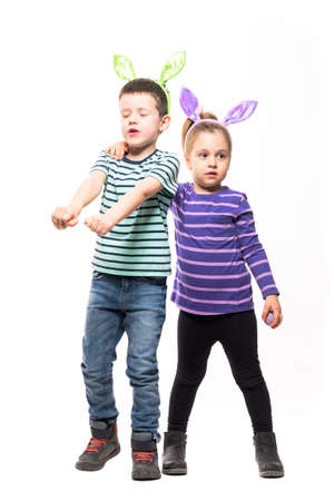 Cute funny excited boy dancing with closed eyes hugged by confused young girl. Easter theme. Full body isolated on white background