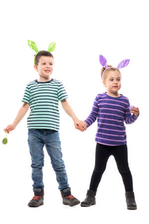 Adorable little kids boy and girl holding hands with painted Easter eggs smiling excited. Full body isolated on white background Stockfoto