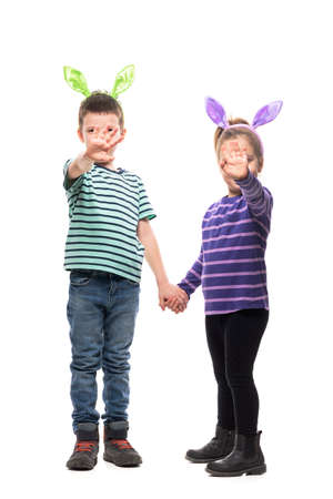 Two kids boy and girl holding hands waving at camera with easter bunny ears. Full body isolated on white background