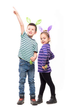 Easter kids excited boy pointing finger up cute girl posing at camera. Full body isolated on white background Stockfoto