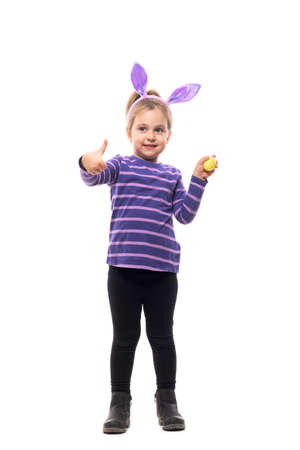Cute little girl with Easter bunny ears looking up holding painted egg showing thumb up. Full body isolated on white background