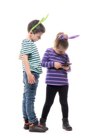 Easter kids with bunny hat using cell phone searching or browsing application. Full body isolated on white background