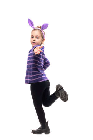 Playful young girl with Easter bunny ears running and reaching hand to camera. Side view. Full body isolated on white background