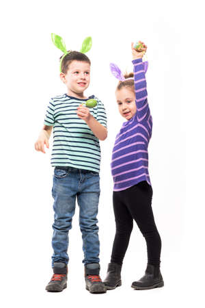 Cute candid happy young kids boy and girl with bunny hat and Easter painted eggs. Full body isolated on white background