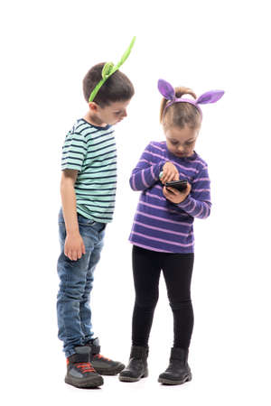 Curious young boy and girl with smartphone using touch screen wearing bunny ears. Full body isolated on white background