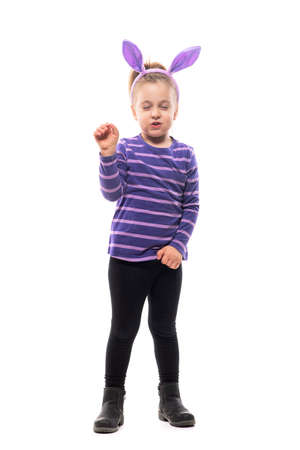 Enthusiastic Easter anticipating young girl child with closed eyes and clenched fists. Full body isolated on white background