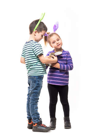 Boy and girl with Easter bunny ears playing with straw rabbit toy. Full body isolated on white background