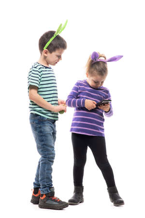 Playful curious children with Easter bunny ears young  smartphone technology. Full body isolated on white background