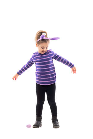 Happy dancing girl child spinning with open hands looking down with bunny ears hat. Full body isolated on white background Stockfoto