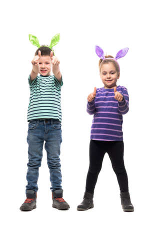 Excited happy kids boy and girl with Easter bunny ears showing thumbs up at camera. Full body isolated on white background Stockfoto