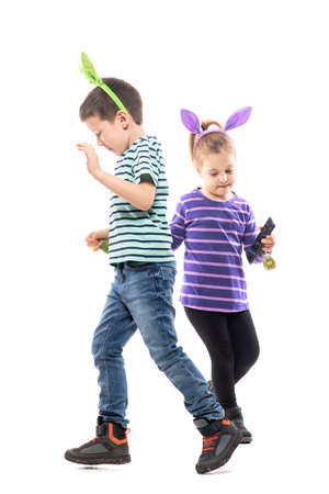 Playful kids with Easter bunny hats listening music dancing in circle and chasing each other. Full body isolated on white background Stockfoto