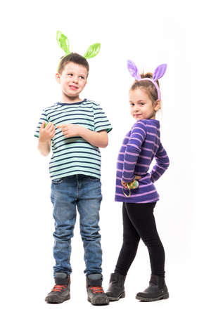 Candid children with Easter bunny ears posing at camera and looking away. Full body isolated on white background Stockfoto