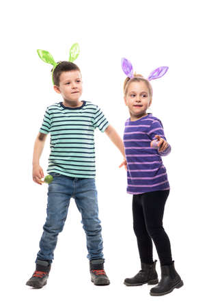 Happy playful young boy and toddler girl holding hands looking away with Easter bunny hat. Full body isolated on white background Stockfoto