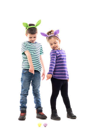 Cute happy boy and girl pointing and eggs on the floor playing Easter hunt. Full body isolated on white background